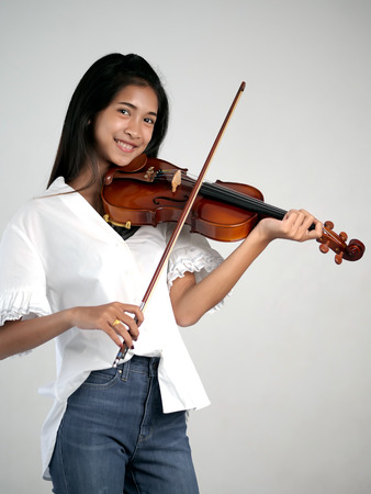 Beautiful Asian woman playing violin, lifestyle concept.