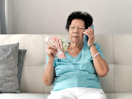 Asian senior woman holding Thai Baht money while talking a phone call, lifestyle concept. Reklamní fotografie