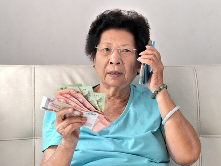 Asian senior woman holding Thai Baht money while talking a phone call, lifestyle concept. Reklamní fotografie