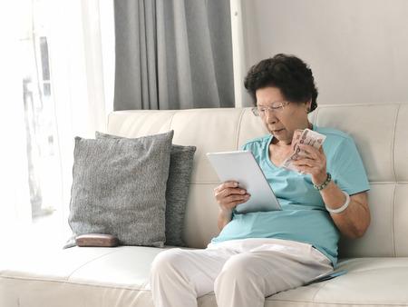 Asian senior woman holding Thai Baht money while using tablet, lifestyle concept. Reklamní fotografie