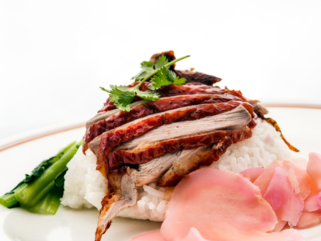 Roast Duck Rice. Popular Chinese barbecue rice dish of rice with slices of roast duck, thick sauce, and choy sum.