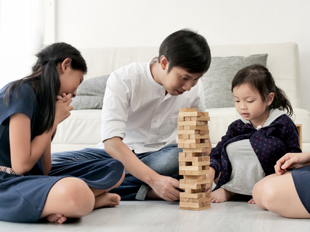Happy Asian family playing wooden blocks together at home, lifestyle concept.
