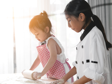 Motion blur kids rolling dough together at home, lifestyle concept. Standard-Bild - 117186495
