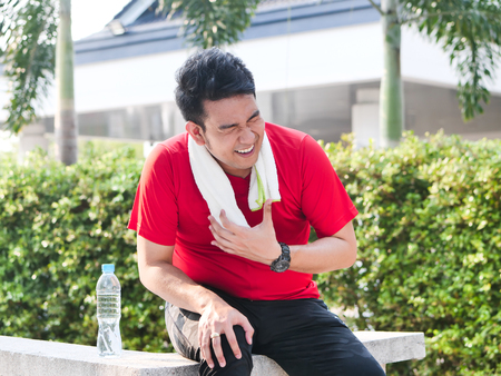 Asian sport hurts his heart while exercise outdoor.