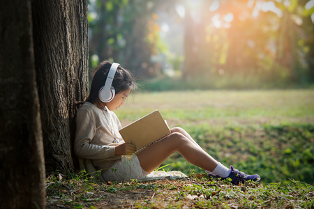 Asian girl with book and headphone siting under the big tree in morning 免版税图像