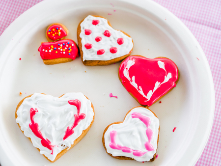 Fresh Homemade Valentine cookies on white plate.