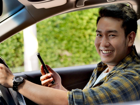 Happy Asian man using smart phone while driving a car, lifestyle concept.