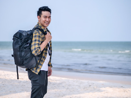 Happy Asian man wih backpack standing at the beach. 스톡 콘텐츠