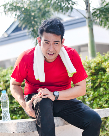 Asian sport man in red t-shirt hurts his leg with accident.
