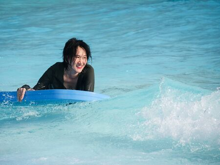 Asian woman playing wave board in water park, lifestyle concept 写真素材 - 128897001
