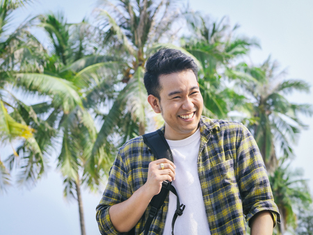 Asian man with backpack smiling at the beach with coconut tree background. 스톡 콘텐츠