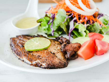 Grilled fish steak with salad with white plate on marble table. Standard-Bild