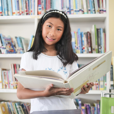 Asian girl holding book with bookshelf background.