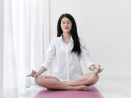 Beautiful asian woman wearing white shirt doing meditation on pink yoga mat at home. Standard-Bild