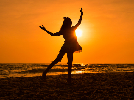 Silhouette girl dancing ballet on the beach in sun rise.