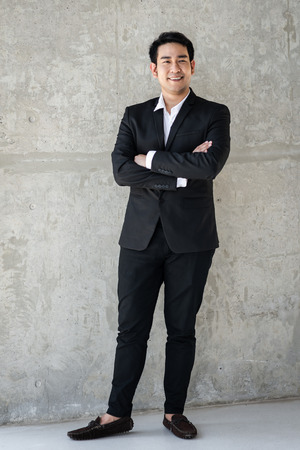 Confident Asian businessman with gray cement background.