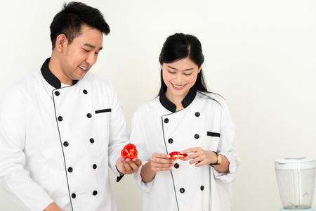 Asian chef man teaching his cook helper for slicing red chili pepper, work lifestyle concept.
