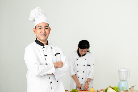 Confident Asian chef looking at camera with his helper background