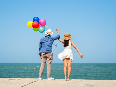 Back of couple holding colorful balloons on the beach in sunny day. Standard-Bild