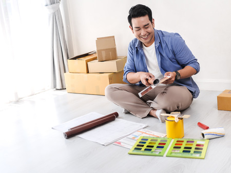 Happy Asian man choosing color palette for his new house.