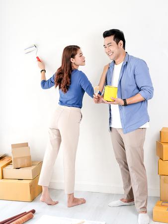 Glückliches asiatisches Paar, das Wand für ihr neues Zuhause malt, Lifestyle-Konzept.