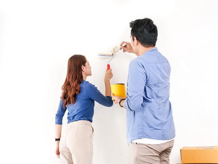 Happy Asian couple painting wall for their new home, lifestyle concept.