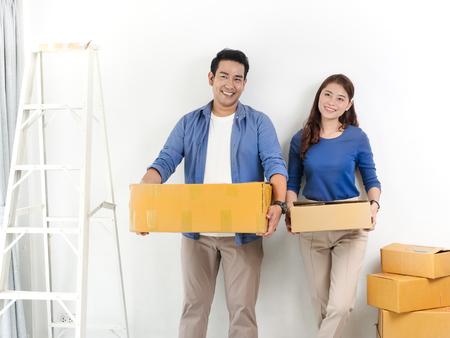 Feliz pareja asiática sosteniendo cajas marrones y mudarse a la nueva casa, concepto de estilo de vida.