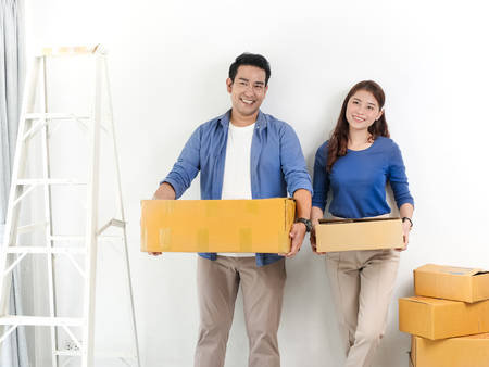 Happy Asian couple holding brown boxes and moving to new house, lifesetyle concept.