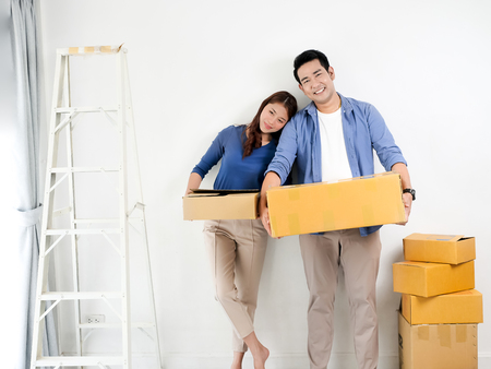 Happy Asian couple holding brown boxes  and moving to new house, lifesetyle concept. 版權商用圖片