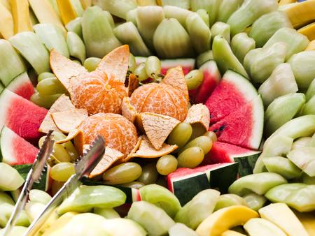 Tropical fruits sliced on  line buffet table. Banco de Imagens
