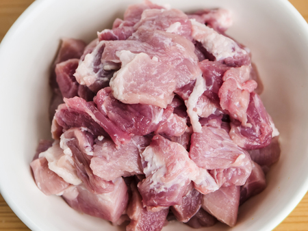Cutting pork meat in bowl on table.