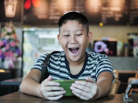 Asian boy using smartphone in coffee shop, lifestyle concept. Фото со стока