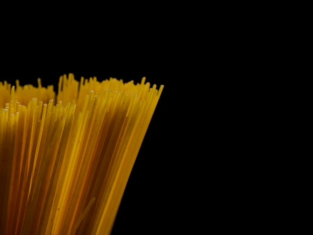Grop of raw spaghetti on black background, copy space for text.