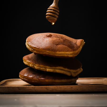 Pancake with honey syrup dipper and black background.