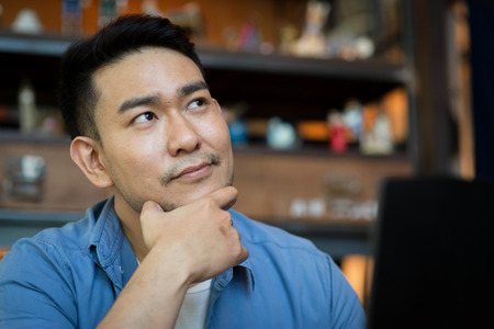 Asian man in deep thought closeup in profile with laptop.