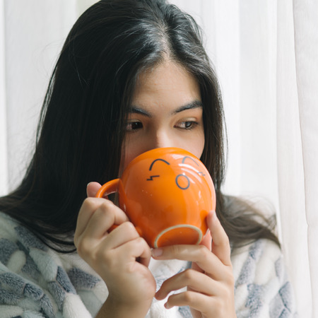 Asian teenager drinking some drink in orange cup near window, lifestyle concept.