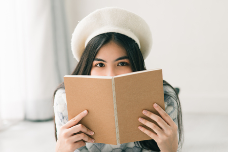 Beautiful teenager girl wearing sweater and reading a book on floor with hiding her face. 스톡 콘텐츠