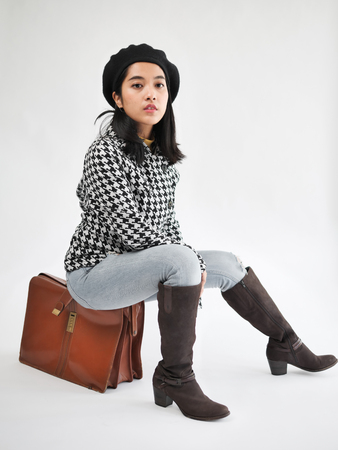 Portrait of Asian woman wearing winter jacket and sitting on vintage brown bag, winter lifestyle fashion.
