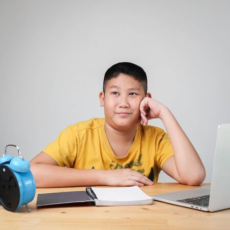 Asian preteen boy doing homework with laptop with blue alarm clock on table.