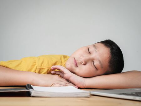 Sleeping Asian preteen boy whild doing homework at home, lifestyle concept.