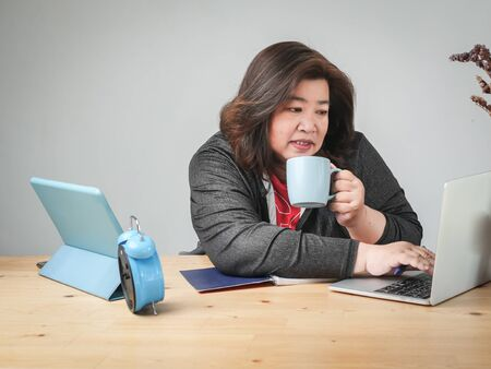 Asian fat woman working and drinking coffee wat home, lifestyle concept. Banco de Imagens