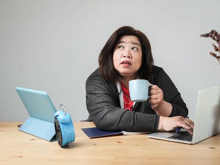 Asian fat woman working and drinking coffee wat home, lifestyle concept. Stock Photo