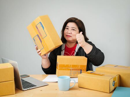 Fat Asian woman packing goods for selling online, delivery concept.