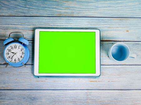 Green screen tablet computer, blue alarm clock and coffee mug on blue wooden background.