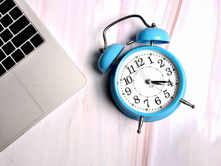Blue alarm clock and laptop on marble background, concept.