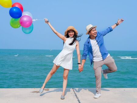 Asian couple holding colorful balloons on the beach in sunny day.
