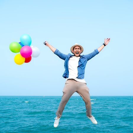 Happy Asian man holding colorful balloons and jumping against blue sky and ocean.