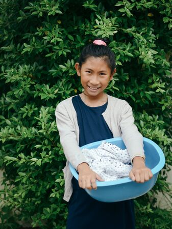 Asian girl holding blue clothes basin with green tree background, lifestyle concept. Stok Fotoğraf
