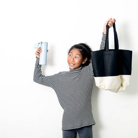 Asian girl holding fabric handbag and water drink bottle eco waste zero living concept. Foto de archivo