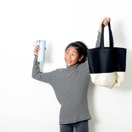 Fille asiatique tenant un sac à main en tissu et une bouteille de boisson d'eau concept de vie zéro déchet écologique.